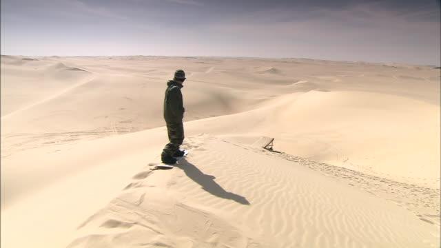 vídeos de stock, filmes e b-roll de a snowboarder gyrates before a slide down a sand dune and a jump from a ramp. - duna