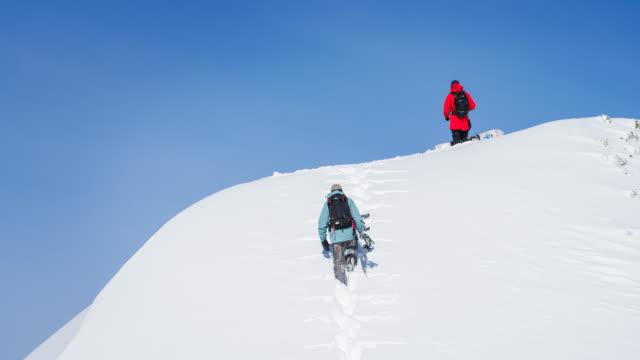 snowboarder wandern bergauf verschneiten bergen - snowboardfahren stock-videos und b-roll-filmmaterial