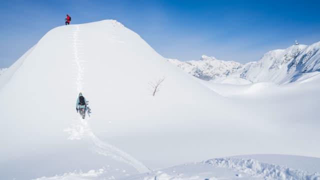vidéos et rushes de montagne enneigée en montée de snowboarder randonnée - qui monte