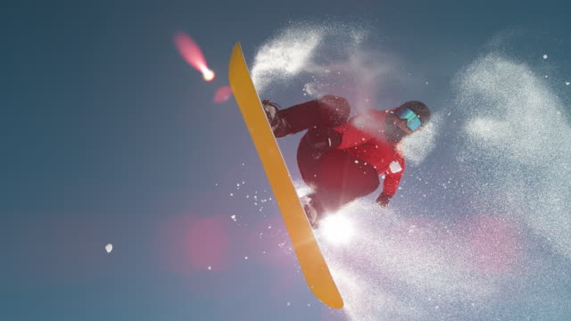SLOW MOTION CLOSE UP: snowboarder jumping and flying over sun on clear blue sky