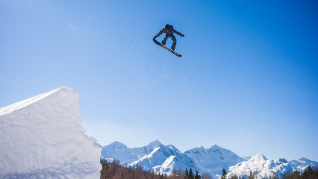 snowboarder jumping in a snowpark - snowboard video stock e b–roll