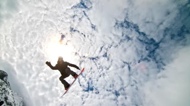 slo-mo-snowboarder springt in der half-pipe mit sonne im hintergrund - halfpipe stock-videos und b-roll-filmmaterial
