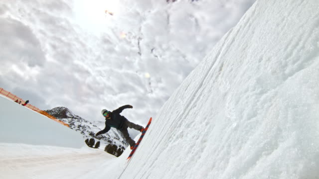 slo mo snowboarder jumping into the air in the half-pipe - half pipe stock videos & royalty-free footage