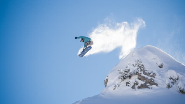 snowboarder jumping off a cliff, landing on freshly fallen snow - snow cornice stock videos and b-roll footage