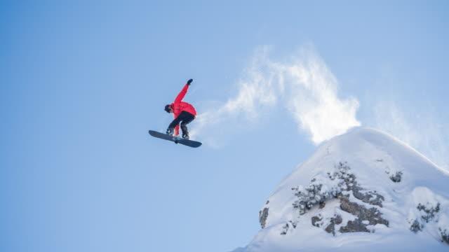 snowboarder springen auf einer klippe - skifahren stock-videos und b-roll-filmmaterial