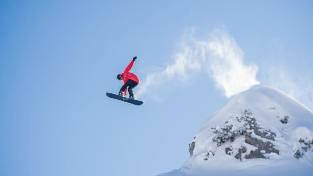 snowboarder jumping off a cliff, landing on freshly fallen snow - powder snow stock videos & royalty-free footage