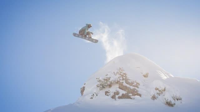 vídeos y material grabado en eventos de stock de snowboarder saltar desde un acantilado, girando en el aire y aterrizando en la nieve recién caída - alcanzar