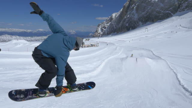pov snowboard saltando su kickers - snowboard video stock e b–roll