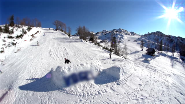 snowboarder jumping while looking into the camera - snowboard stock videos and b-roll footage