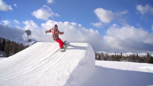 snowboarder jumps in a snowpark - snowboarding stock videos & royalty-free footage