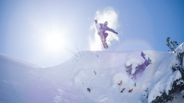 vídeos de stock e filmes b-roll de snowboarder jumps on freshly fallen snow - leisure equipment
