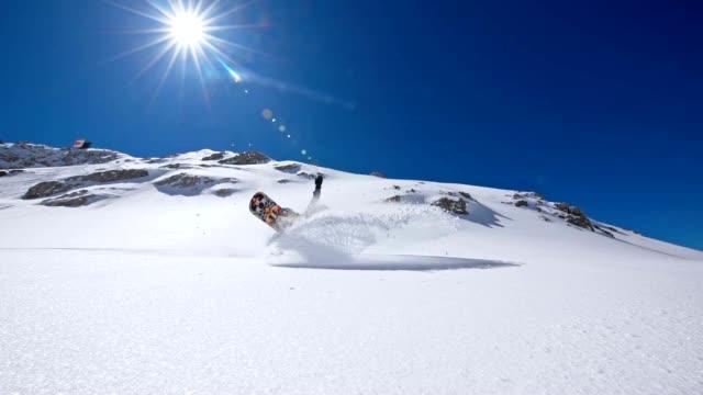 SLO MO Snowboarder knocking snow at the camera