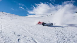 Snowboarder making an unsuccessful turn, falling on the ski slope