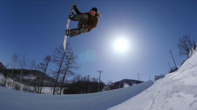 snowboarder on a bank of japan's largest halfpipe at ban.k hokkaido - スノーボード点の映像素材/bロール