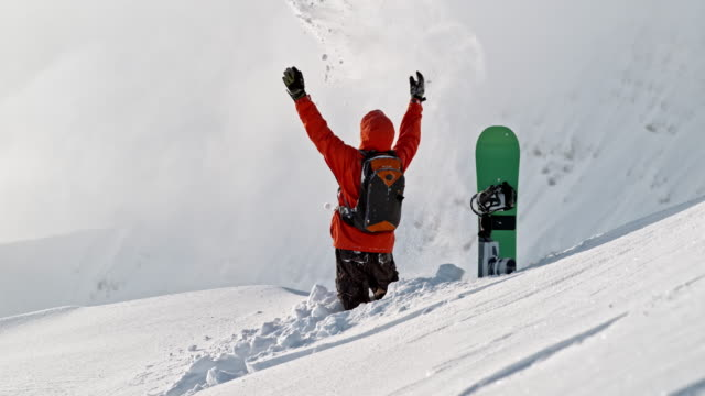 SLO MO Snowboarder on a mountain top throwing snow into the air