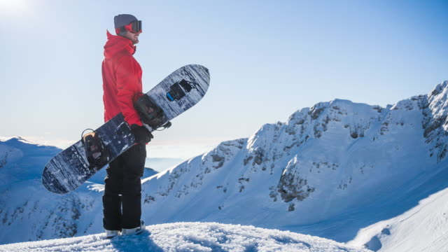 snowboarder on top of mountain enjoying the view of winter landscape on a sunny day - snowboard video stock e b–roll