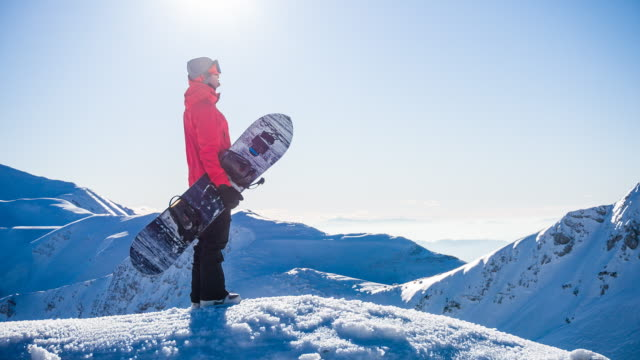 snowboarder on top of mountain enjoying the view of winter landscape on a sunny day - winter sport stock videos and b-roll footage
