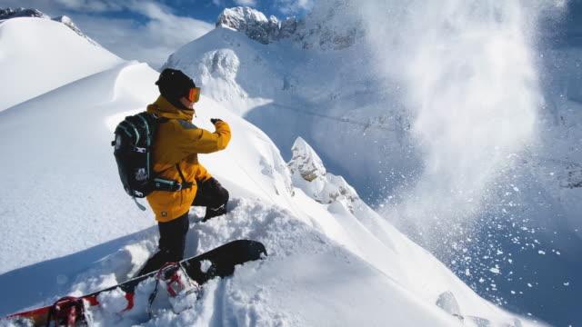 snowboarder auf dem berg wirft schnee in die luft an einem schönen sonnigen wintertag - schneeverwehung stock-videos und b-roll-filmmaterial