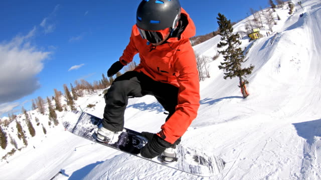 snowboarder performing a trick, jumping and turning mid-air in a snowpark - snowboard video stock e b–roll