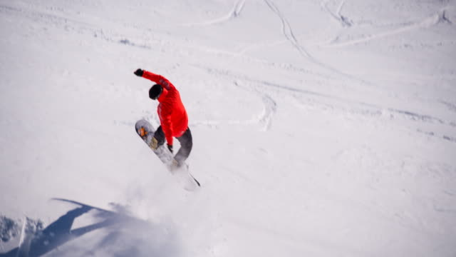 stockvideo's en b-roll-footage met snowboarder uitvoeren van een truc op de skipiste - stunt