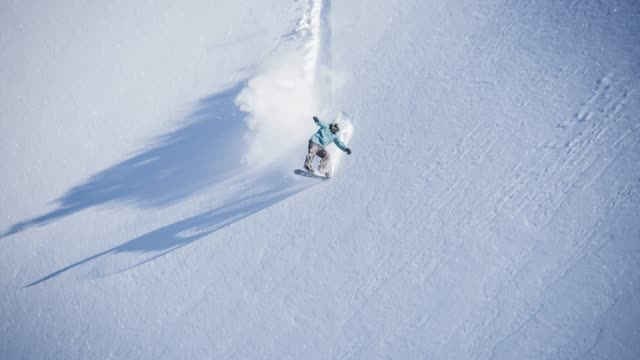 snowboarder performing a trick while riding powder snow downhill - snowboarding stock videos & royalty-free footage