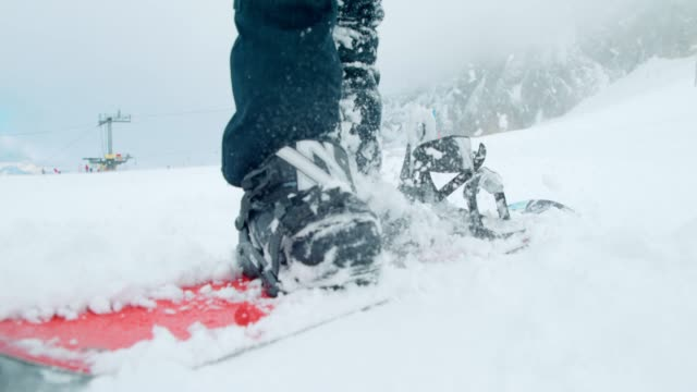 slo mo snowboarder preparing for winter adventure - boot stock videos & royalty-free footage
