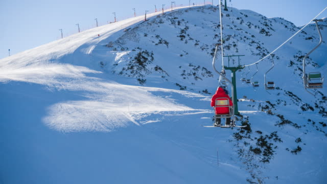 Snowboarder riding a ski lift to the top of the snowcapped mountain