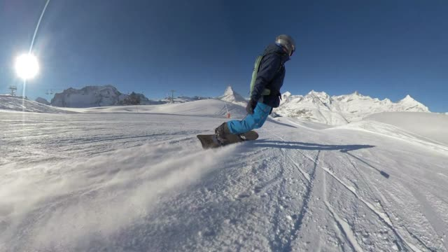snowboarder riding down a hill with the matterhorn - sci e snowboard video stock e b–roll