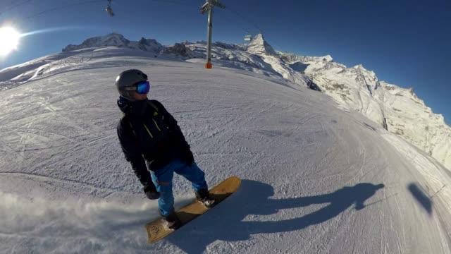 snowboarder fahren auf einem hügel mit dem matterhorn - extremsport stock-videos und b-roll-filmmaterial
