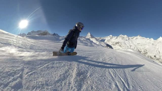Snowboarder riding down a hill with the Matterhorn