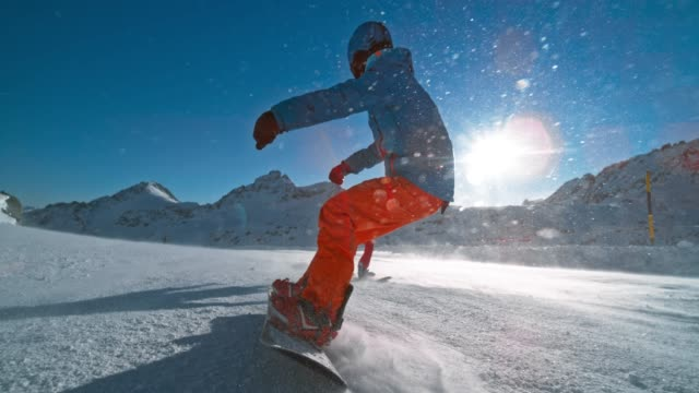 slo mo ts snowboarder riding down a piste behind a friend on a sunny day in the mountains - snowboarding stock videos & royalty-free footage