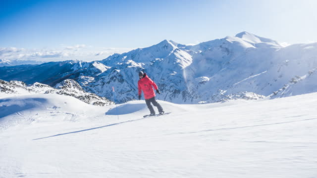 Snowboarder riding down an idyllic mountain ski resort piste on a perfect sunny winter day