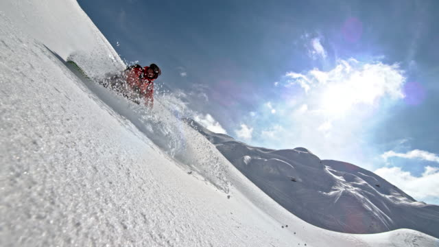 SLO MO Snowboarder riding down the mountain slope in powder snow on a sunny day