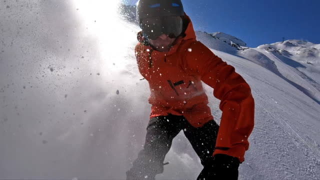 snowboarder riding down the ski piste spraying snow while making a turn - skiing and snowboarding stock videos and b-roll footage