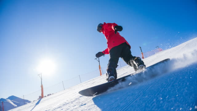 snowboarder riding down the ski slope on a sunny day - snowboard stock videos and b-roll footage