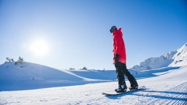 Snowboarder riding down the ski slope on a sunny day