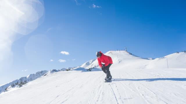 stockvideo's en b-roll-footage met snowboarder rijden onderaan de skipiste op een zonnige dag met skilift op achtergrond - skivakantie