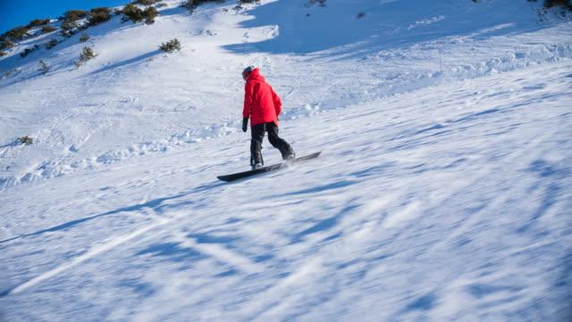 stockvideo's en b-roll-footage met snowboarder rijden van de skipiste op een zonnige winterdag - skivakantie