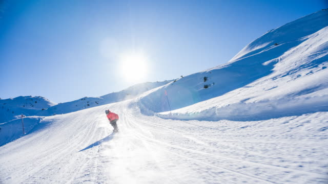 snowboarder riding down the ski slope with snow spraying towards him on a sunny day - skiing and snowboarding stock videos and b-roll footage