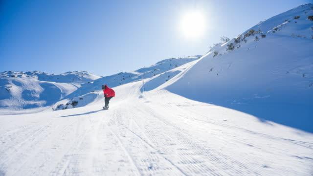 stockvideo's en b-roll-footage met snowboarder bergafwaarts rijden, crouching te verwerven meer snelheid - skivakantie