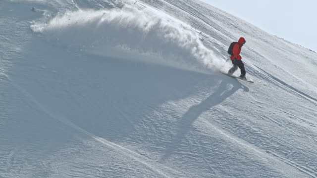 SLO MO Snowboarder riding off-piste on a sunny day