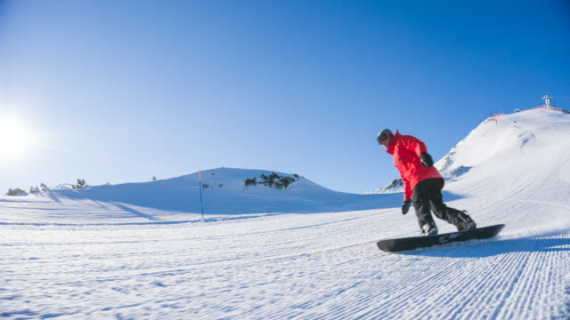 stockvideo's en b-roll-footage met snowboarder rijden op de skipiste in mountain resort - skivakantie
