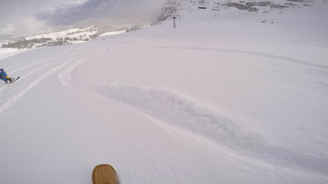 snowboarder riding powder behind skier - snowboarding stock videos and b-roll footage
