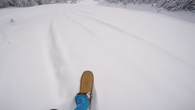 snowboarder riding powder behind skier - snowboarding stock videos & royalty-free footage