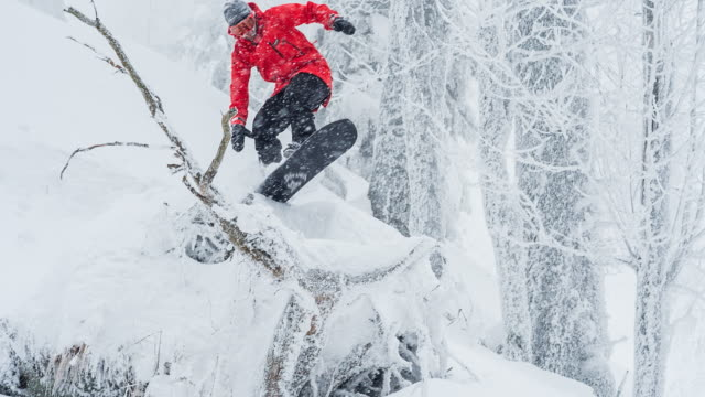 snowboarder riding powder snow on snowy winter day - snowboard stock videos and b-roll footage