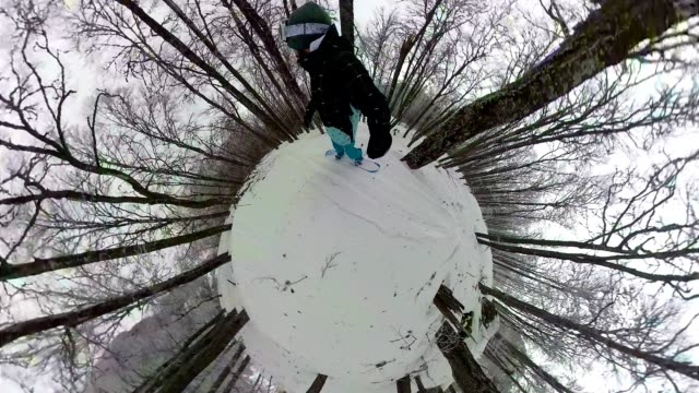 Snowboarder riding through a snowy mountain forest