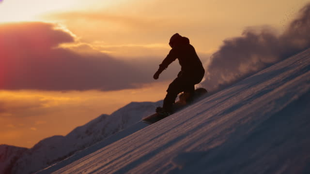 SLO MO TS Snowboarder silhouette riding the slope at sunset