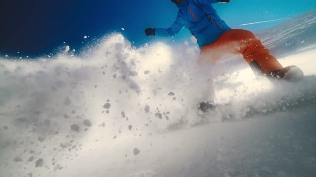 slo mo snowboarder splashing powdered snow into the camera in sunshine - powder snow stock videos and b-roll footage