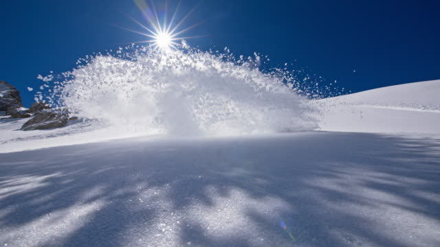 slo mo snowboarder spraying snow at the camera - winter sport stock videos and b-roll footage