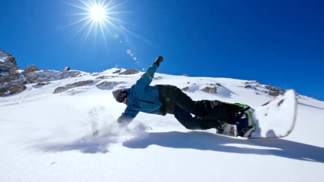 slo mo snowboarder spraying snow at the camera - snowboarding stock videos & royalty-free footage